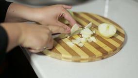 Den kvinnliga handen med en kniv klippte lökar på en skärbräda arkivfilmer