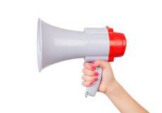 Den kvinnliga handen med rosa färger spikar att rymma en megafon fotografering för bildbyråer