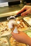 Den kvinnliga handen med skopan tar glass från kylen och portionen i dillandekotte Kvinna som tar skopan av smaklig glass Royaltyfri Foto