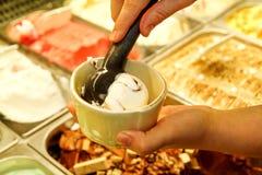 Den kvinnliga handen med skopan tar glass från kylen och portionen i keramiska vita koppar Arkivfoto