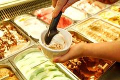 Den kvinnliga handen med skopan tar glass från kylen och portionen i keramiska vita koppar Royaltyfri Bild