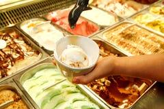 Den kvinnliga handen med skopan tar glass från kylen och portionen i keramiska vita koppar Arkivbilder