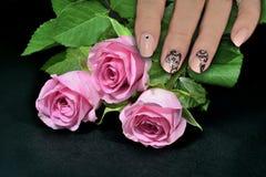 Den kvinnliga handen med spikar konstmanikyr- och rosa färgrosor Royaltyfri Bild