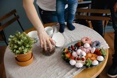 Den kvinnliga handen rymmer kaffebönor och sparar från att falla ner Härlig och färgrik blandning av sefir och frukter på en tabe royaltyfri bild