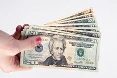 Den kvinnliga handen rymmer kontantbetalningvaluta tjugo dollar pengar Arkivfoton
