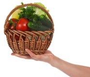 Den kvinnliga handen rymmer korgen med grönsaker arkivbild
