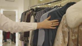 Den kvinnliga handen rymmer på mode som märkes- kläder på en bödel i shoppar lager videofilmer