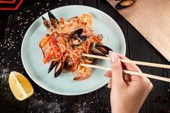 Den kvinnliga handen rymmer pinnar för att äta kinesiska nudlar med musslor royaltyfria bilder