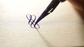 Den kvinnliga handen skriver en penna calligraphic tecken lager videofilmer