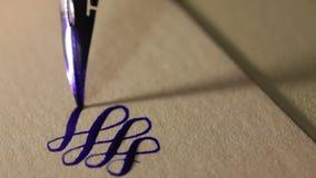 Den kvinnliga handen skriver en penna calligraphic tecken arkivfilmer