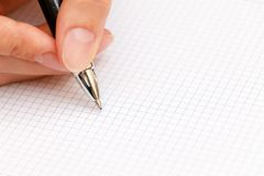 Den kvinnliga handen skriver en penna i anteckningsbok Royaltyfri Foto