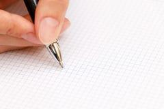 Den kvinnliga handen skriver en penna i anteckningsbok Royaltyfri Bild