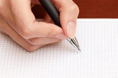 Den kvinnliga handen skriver en penna i anteckningsbok Royaltyfri Fotografi