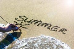 Den kvinnliga handen skriver på sanden ordsommaren royaltyfri foto