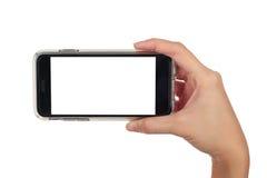 Den kvinnliga handen som rymmer den horisontalsmarta telefonen, använder den snabba banan Arkivfoton