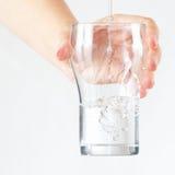 Den kvinnliga handen som rymmer ett exponeringsglas av sötvatten, hälls Arkivbild