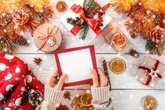 Den kvinnliga handen som skrivar ett brev till jultomten på vit träbakgrund med julgåvor, granfilialer, tröja, sörjer kottar arkivfoton
