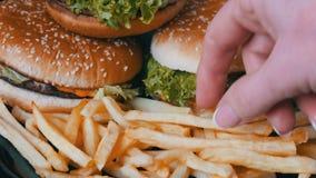 Den kvinnliga handen tar småfiskar för en fransman på bakgrund av enorma hamburgare lager videofilmer