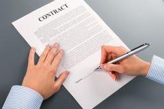 Den kvinnliga handen undertecknar lånavtalet Arkivbild
