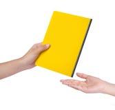 Den kvinnliga handen överför en gul bok Arkivfoton