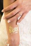 Den kvinnliga handshowvigselringen och textbruden blänker guld- tatt royaltyfri foto