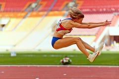 Den kvinnliga idrottsman nen gör längdhopp Arkivbild