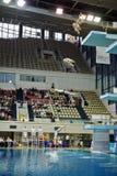 Den kvinnliga idrottsman nen hoppar från dykningtorn Arkivfoto