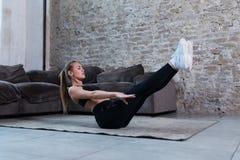 Den kvinnliga idrottsman nen som gör den statiska hållövningen för abs som V förstärker kärna, tränga sig in på golv i vindstudio Royaltyfri Bild