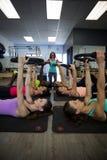 Den kvinnliga instruktören som hjälper gruppen av kvinnor med pilates, ringer övning royaltyfri fotografi