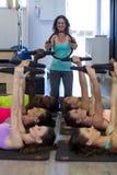Den kvinnliga instruktören som hjälper gruppen av kvinnor med pilates, ringer övning royaltyfria foton