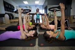 Den kvinnliga instruktören som hjälper gruppen av kvinnor med pilates, ringer övning royaltyfri foto