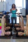 Den kvinnliga instruktören som hjälper gruppen av kvinnor med pilates, ringer övning arkivfoto