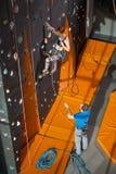 Den kvinnliga klättraren klättrar upp på den inomhus vagga-klättringen väggen royaltyfri bild