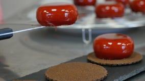 Den kvinnliga kocken lägger ut en kaka på en platta, efterrättpresentation Efterrätt dekorerade kakor lager videofilmer