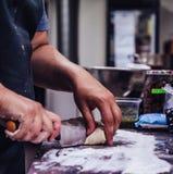 Den kvinnliga kocken Preparing Bread Dough för själv gjorde bröd och små pastejer arkivbild