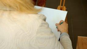 Den kvinnliga konstnären drar en blyertspenna skissar i konststudio Arkivbilder