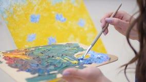 Den kvinnliga konstnären förbereder höger skugga av blått lager videofilmer