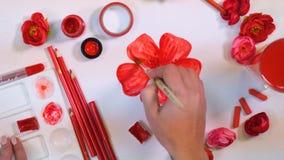 Den kvinnliga konstnären räcker att dra den röda blomman Idérikt konstnärskrivbord från över lager videofilmer