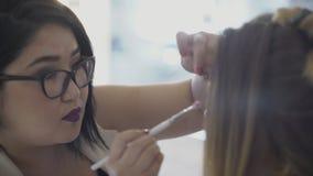 Den kvinnliga konstnären sätter skuggor på ögon av den placerade kvinnan i skönhetstudio arkivfilmer