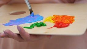 Den kvinnliga konstnären som målar en bild som blandar färgar tätt upp 4K stock video