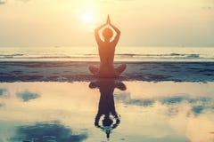 Den kvinnliga konturn i yoga med reflexionen i vatten, meditation poserar på solnedgången Arkivfoto