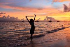 Den kvinnliga konturn på bakgrunden av havssolnedgången, avkoppling, semesterfolk Arkivbild