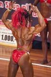 Den kvinnliga kroppsbyggaren i baksidadubblettbiceps poserar och den röda bikinin Royaltyfria Bilder