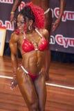 Den kvinnliga kroppsbyggaren i triceps poserar och den röda bikinin Arkivfoton