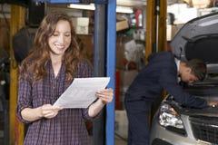 Den kvinnliga kunden i auto reparation shoppar tillfredsställt med Bill For Car Fotografering för Bildbyråer