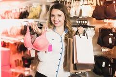 Den kvinnliga kunden som visar hennes köp i underkläder, shoppar Royaltyfri Bild