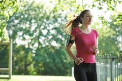 Den kvinnliga löparen parkerar in med Wearable teknologi arkivfoton
