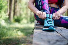Den kvinnliga löparen som binder skon, snör åt i parkera Sund livsstil fotografering för bildbyråer