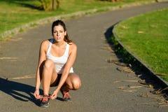 Den kvinnliga löparen som snör åt sportskor, innan han kör in, parkerar royaltyfri bild