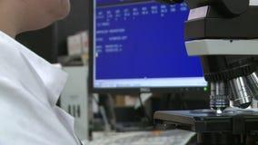 Den kvinnliga labbteknikeren ser till och med mikroskop (3 av 3) stock video